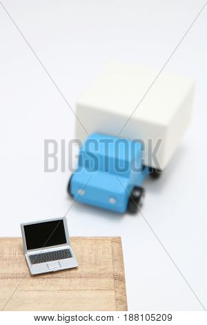 Toy car truck and laptop on white background.  logistics, distribution, and delivery concept.