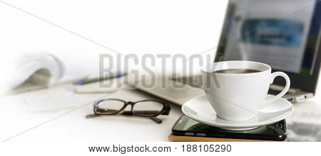 Coffee cup on an office desk with cell phone laptop glasses and papers blurred background fades to white panoramic banner format for web page header copy space selected focus narrow depth of field