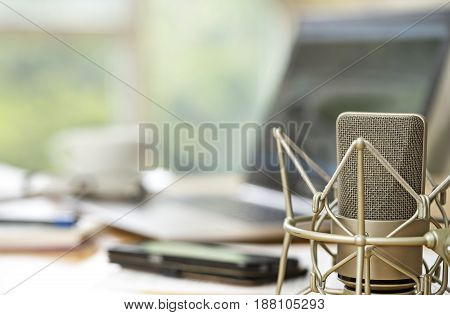 condenser microphone close up in front of a blurred workspace with laptop cellphone and notepad on a desktop concept for international journalism media or radio interview copy space in the background selected focus narrow depth of field