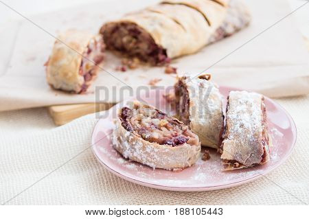 Three pieces traditional apple strudel dusted with powdered sugar on rosa plate