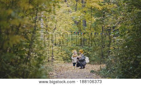 Baby girl with her mother and Teddy Bear walking in autumn park, telephoto