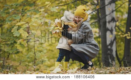 Woman with little daughter in autumn park, telephoto