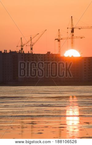 The disk of the sun falls for the houses under construction on the shore of the lake