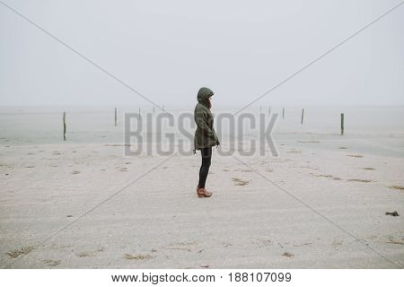 Woman standing on an empty beach. Bad weather.