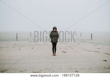 Woman standing on empty beach in winter time