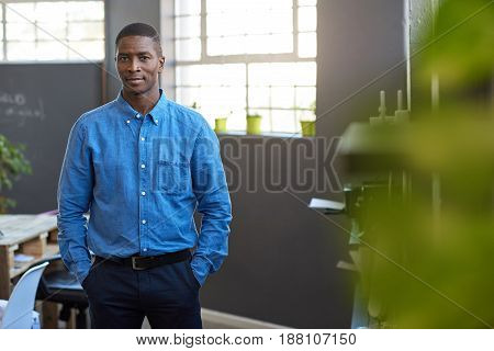 Portrait of a focused and confident young African businessman while standing with his hands in his pockets in a large modern office