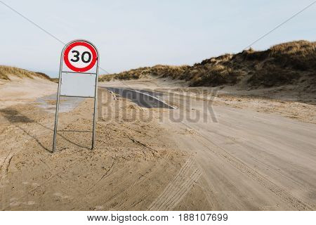 Asphalt road covered with sand and 30km/h sign