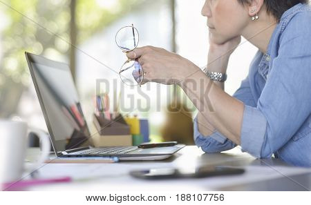 Businesswoman working in office with laptop computer Selective focus on hand holding glasses