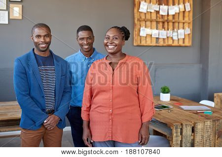 Portrait of three smiling young African business colleagues standing confidently while working together in a large modern office
