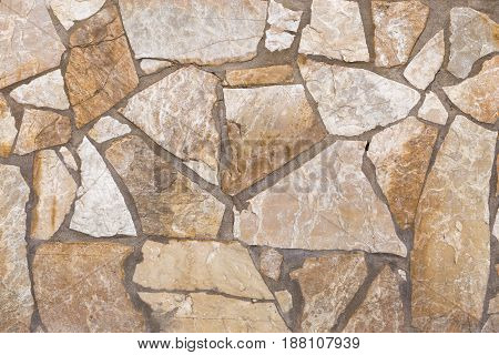 Wall of stones of brown and white colors. Front view