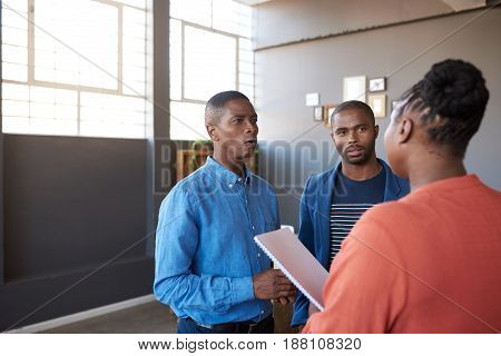 Three casually dressed young African work colleagues deep in discussion together while standing in a large modern office