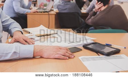 Office: man in blue shirt is discussing financial report using data and gadget, defocused