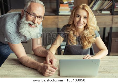 Casual Middle Aged Couple Working On Laptop Together
