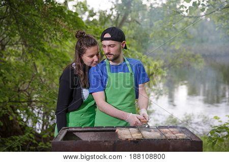 Young couple preparing meat on a grill outdoors
