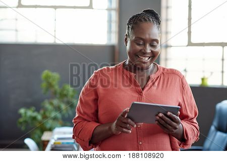 Casually dressed young African businesswoman smiling and using a digital tablet while standing alone in a modern office
