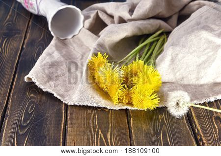 Dandelions and vase. Vase white fell on the table. The table surface of planks. A bouquet of flowers yellow dandelion lying on the table next to the white vase.