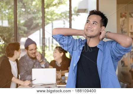 Happy young businessman is relaxing in his office