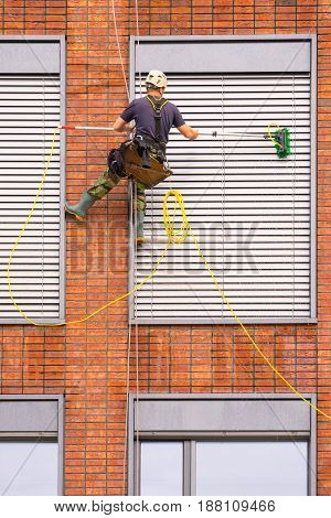 Cleaning windows building facade with worker at height man at work
