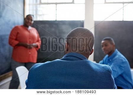 Rearveiw of an African businessman sitting in a bright modern office listening to a presentation on a chalkboard by a colleague
