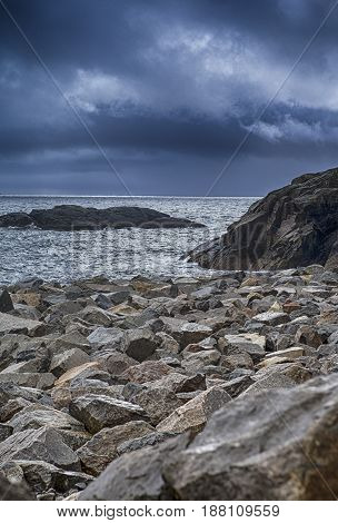 Picturesque Stony Shore At Lofoten Islands in Norway Against Dramatic Blue Sky.Vertical Image Composition
