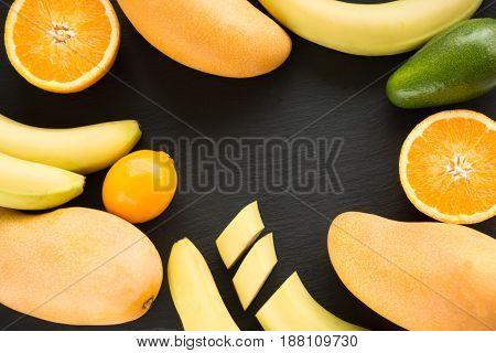 Fresh tropical fruit, mango , banana, orange, lemon, avocado around on black slate dish. View from above. Space for text.