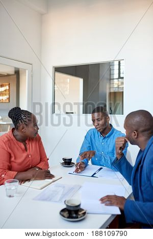 Group of focused young African office colleagues sitting together at a table in a modern office discussing paperwork