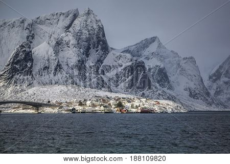 Traditional Village Reine at Lofoten Islands During Sunset Against Snowy Mountains in Norway. Horizontal Image