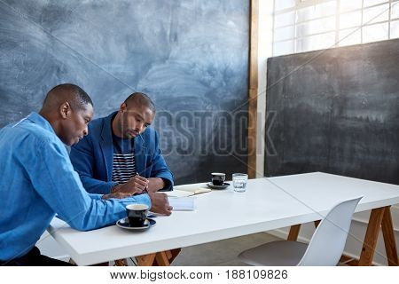 Two focused young African businessmen sitting together at a table in a modern office discussing paperwork during a meeting
