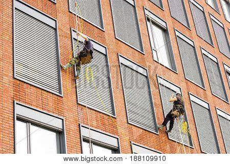 Building facade with two cleaners 2 men working at heights