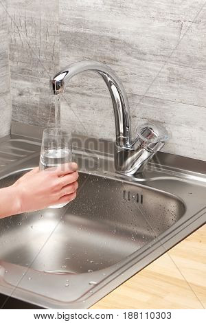 Female Hand Holding Glass Under Tap Water Against Kitchen Sink