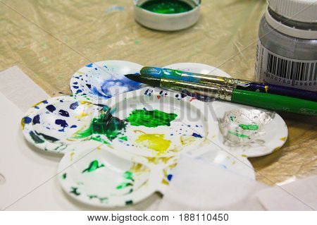 Palette with brush and colored ink drops on the table. The brush lying on the palette with paints