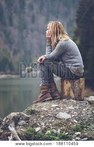 vertical side view portrait of Caucasian young blonde woman with light colored sweater and jeans holding a tree branch and meditating relaxing alone on a tree stump in front of a lake surrounded by forest mountains