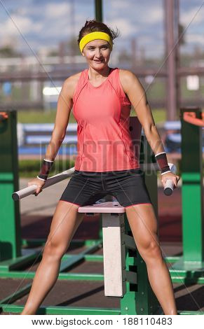 Sport Ideas. Portrait ot Caucasian Brunette Female Athlete in Professional Outfit Having Work Out Exercise Outdoor. Vertical Image Composition