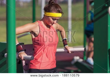 Portrait of Concentrated Caucasian Female Athlete in Professional Training Outfit Having Outdoor Workout Exercises on Weights.Horizontal Shot
