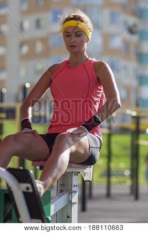 Portrait of Female Athlete in Professional Training Outfit Having Outdoor Workout Exercises on Weights. Vertical Image Orientation