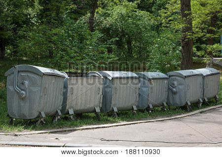 Row of large green wheelie bins for rubbish recycling and garde