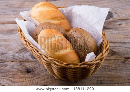 Bread basket with buns on a wooden board
