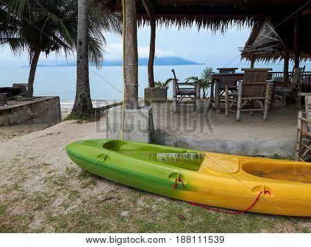 Thailand. Canoe near the sea. Beach restaurant with wooden furniture.