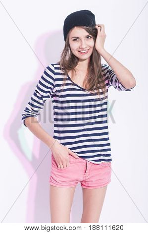 Natural Portrait of Happy Laughing Caucasian Brunette Girl in Hat and Striped Shirt. Posing Against White Background. Vertical Shot