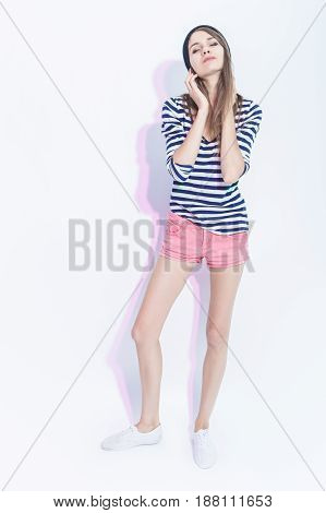 Full Length Portrait of Romantic Caucasian Brunette Girl in Hat and Striped Shirt. Hands Lifted and Touching Head. Vertical Image