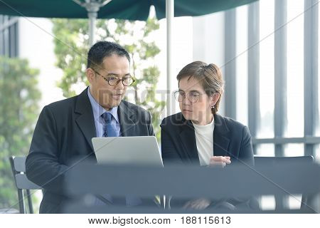 Executive businessman and woman discussing and working together during a meeting at outdoor cafe
