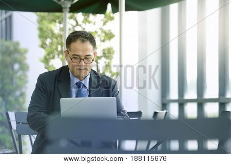 Executive businessman working with laptop computer at outdoor cafe