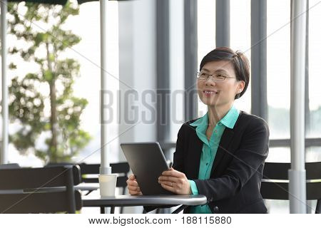 Asian businesswoman working with tablet computer at outdoor cafe