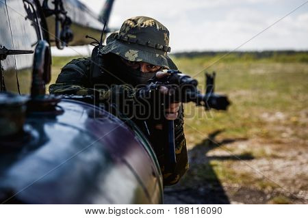 Photo of a soldier with an automatic rifle at a helicopter