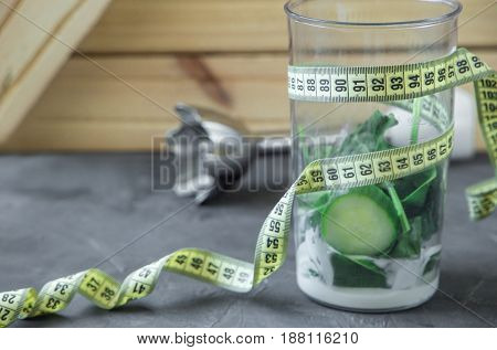 Blender full of vegetables and yogurt and meter. 90 60 90 concept on dark background