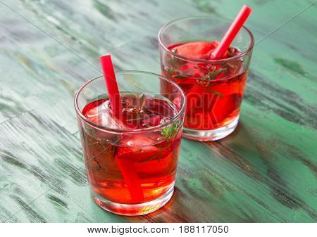 Summer refreshing cocktails with strawberry, ice and thyme on a light green wooden table