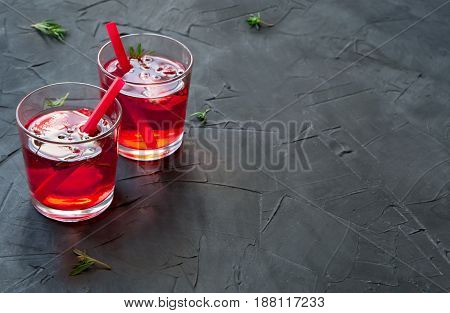 Summer refreshing cocktails with strawberry, ice and thyme on a concrete background. space for text