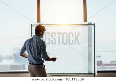 Businessman using whiteboard to present ideas for business decision making. Entrepreneur making a business presentation in office.