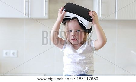 Little Girl Uses a Virtual Reality Glasses in The Kitchen