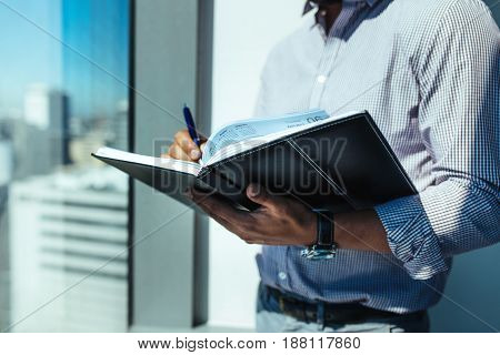 Businessman holding an open diary standing beside a window in office. Man doing office work standing in sunshine near window of highrise office building overlooking the cityscape.